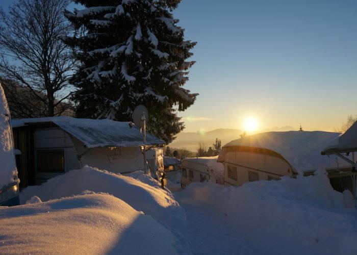 Sonnenaufgang über dem winterlichen Campingplatz in Vorarlberg